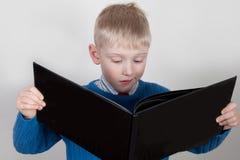 Le jeune garçon lit le grand livre Photographie stock