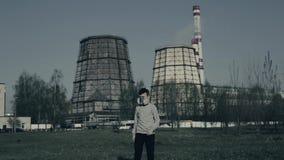 Le jeune garçon marche devant des cheminées d'usine Pollution atmosph?rique Portrait haut étroit de jeune usine de witn de type s banque de vidéos