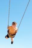 Le jeune garçon mignon balance à la cour de jeu Image libre de droits
