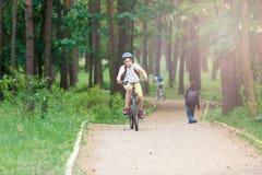 Le jeune garçon mignon dans le casque monte une bicyclette en parc Le garçon va sur la route sport images libres de droits