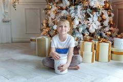 Le jeune garçon ouvre un cadeau sous un arbre de Noël Image stock