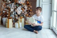 Le jeune garçon ouvre un cadeau sous un arbre de Noël Photographie stock