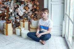 Le jeune garçon ouvre un cadeau sous un arbre de Noël Images stock