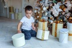 Le jeune garçon ouvre un cadeau sous un arbre de Noël Photo stock