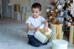 Le jeune garçon ouvre un cadeau sous un arbre de Noël Images libres de droits