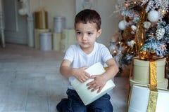 Le jeune garçon ouvre un cadeau sous un arbre de Noël Image libre de droits