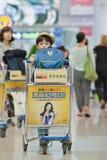Le jeune garçon pousse un chariot à bagages à l'aéroport d'Icheon, Séoul, Corée du Sud Image libre de droits