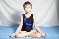 Le jeune garçon pratique le yoga Photo stock