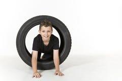 Le jeune garçon rampe par un pneu Image stock