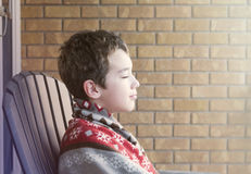 Le jeune garçon s'asseyant sur le porche observe fermé, enveloppé dans la couverture apprécient image libre de droits