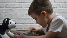 Le jeune garçon s'asseyant sur le plancher pressant le terminal de position se boutonne Technologies modernes pour des enfants Pr banque de vidéos
