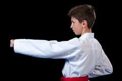 Le jeune garçon s'est habillé dans un kimono blanc de karaté avec la ceinture rouge images stock