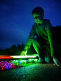 Le jeune garçon se met à genoux à côté de la planche à roulettes d'éclairage avec le mouvement sur la longue exposition Image libre de droits