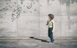 Le jeune garçon se tenant à côté du mur gris Image libre de droits