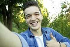 Le jeune garçon souriant au parc prend le selfie photographie stock libre de droits