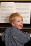 Le jeune garçon joue le piano Images libres de droits