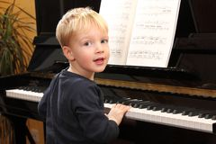 Le jeune garçon joue le piano Image stock