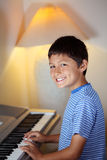 Le jeune garçon joue un piano Image stock