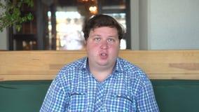 Le jeune gros homme dans la chemise parlent quelque chose sur l'appareil-photo fond occasionnel audition bâti clips vidéos