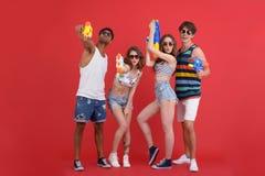 Le jeune groupe d'amis avec le jouet de l'eau lance Photo stock