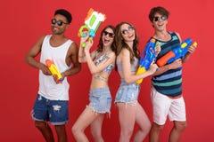 Le jeune groupe d'amis avec le jouet de l'eau lance Photos libres de droits