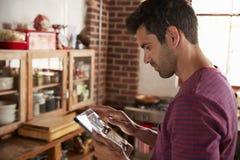 Le jeune homme à l'aide de la tablette dans la cuisine, se ferment  Photos stock