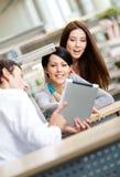 Le jeune homme à la bibliothèque affiche la tablette à deux femmes Photo libre de droits