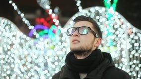 Le jeune homme élégant à célèbrent de la nouvelle année, lumières et l'arbre de Noël de ville s'est reflété dans les verres banque de vidéos
