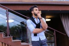 Le jeune homme élégant concentré de l'aspect musulman regarde de s Photo libre de droits