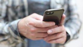 Le jeune homme élégant dans une chemise de plaid utilise un smartphone clips vidéos