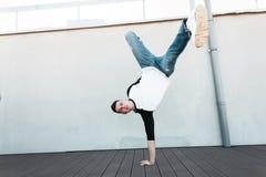 Le jeune homme élégant de danseur dans des jeans dans une chemise à la mode se tient sur la main dehors Danse de coupure belle de photographie stock