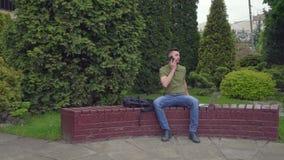 Le jeune homme élégant se sent déprimé pendant la conversation mobile banque de vidéos