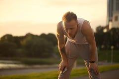 Le jeune homme énergique font les exercices et le runnig avec le téléphone et le m image libre de droits