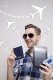 Le jeune homme adulte réserve le billet de déplacement par l'intermédiaire du comprimé photo libre de droits