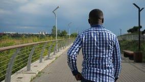 Le jeune homme afro-américain marche en parc de ville dans le jour d'été nuageux banque de vidéos