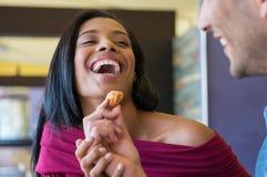 Le jeune homme alimente son amie avec le croissant Photo stock