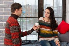 Le jeune homme a apporté le café à son amie tandis qu'elle s'asseyant dessus Photo stock