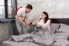 Le jeune homme a apporté le café dans le lit tandis que son amie s'asseyant dedans Image libre de droits