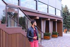 Le jeune homme Arabe attirant regarde autour et les balades, sourit Photo stock
