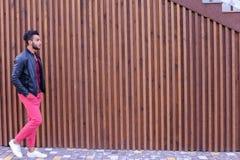 Le jeune homme Arabe attirant regarde autour et les balades, sourit Photo libre de droits