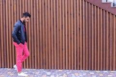 Le jeune homme Arabe attirant regarde autour et les balades, sourit Photos libres de droits