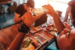 Le jeune homme Arabe prend une photo de sa nourriture pour le réseau social Concept de dépendance d'Internet cuvette de café de g Photographie stock