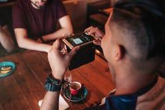 Le jeune homme Arabe prend une photo de son café pour le réseau social Concept de dépendance d'Internet Pause-café en café Photographie stock libre de droits