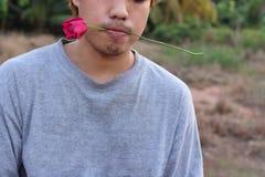 Le jeune homme asiatique bel tient une rose rouge dans sa bouche sur le fond brouillé par nature Conce de jour du ` s de Valentin Photo libre de droits