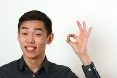 Le jeune homme asiatique de sourire donnant le signe correct et le regardant est venu Image stock