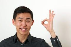 Le jeune homme asiatique de sourire donnant le signe correct et le regardant est venu Photographie stock