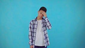 Le jeune homme asiatique faire un facepalm fait des gestes sur le fond bleu banque de vidéos