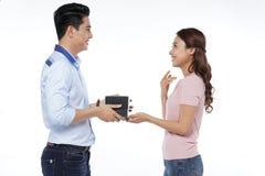 Le jeune homme asiatique proposent à son amie d'isolement sur le dos de blanc Photos stock