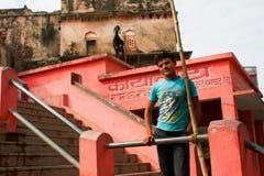 Le jeune homme asiatique se tient sur la rue avec historique Photographie stock