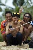 Le jeune homme asiatique utilisant des lunettes de soleil prend le selfie et le rire avec des amis Image stock